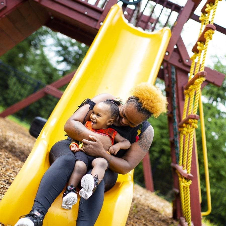 Mother and daughter sit at the end of a yellow slide with a jungle gym behind them.