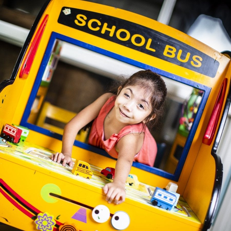 Little girl with a facial deformity plays in a toy school bus.