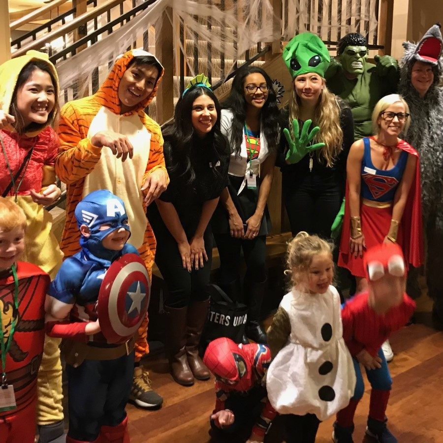 A group of adults and kids dressed in Halloween costumes stands together and smiles.