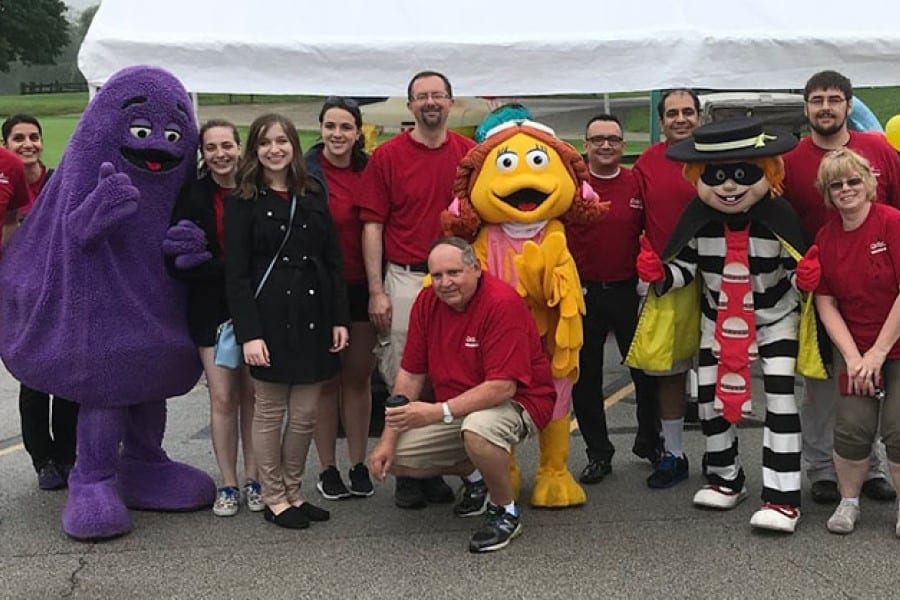 Ten people stand in a row along with characters dressed as McDonald's Grimace and Hamburgler.